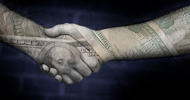 hands shaking within background of images of currency